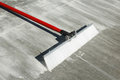 Concrete finishing broom with plastic bristles and red handle Royalty Free Stock Photo