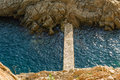 Concrete footbridge linking rocky land with island Stock Image