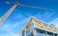 Concrete highrise construction site with tower crane and blue sky background Stock Images