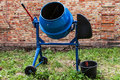 Concrete mixer new blue cement against a brick wall Royalty Free Stock Photos