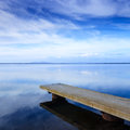 Concrete pier or jetty and on a blue lake and sky reflection on water cloudy Royalty Free Stock Image