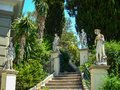 Concrete stairs and concrete statues and big luxurian green vegetation Royalty Free Stock Photo