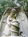 Concrete statue of an angel with a jug in the park Royalty Free Stock Photo