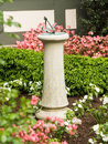 Concrete stone sundial in flower bed or bronze garden of old home Royalty Free Stock Photos