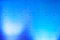 Concrete wall with blue spotlights a a pattern of small holes lit by Royalty Free Stock Photography
