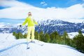 Concurring the mountains happy young woman skier stand on piste slope with mountain and forest on background Royalty Free Stock Images