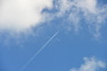 Condensation trails airplane against the blue sky and clouds Stock Images