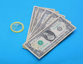 Condom with money against blue background Royalty Free Stock Photography