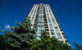 Condominium - place to live, rising tower into blue summer sky. Royalty Free Stock Photo