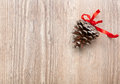 Cone with a red ribbon fir on wooden background Royalty Free Stock Photos