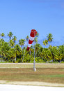 Cone wind measure wind direction in small airfield on the tropical island with palm trees at a runway Royalty Free Stock Photo