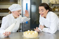 Confectioner apprentice nibbling whipped cream from cake in bakery Stock Images