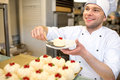 Confectioner with cakes handsome selling in the pastry shop Stock Photography