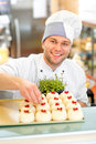 Confectioner with cakes handsome in uniform decorating cake currant Stock Photo