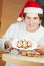 Confectioner in santa hat shows plate with cookies Royalty Free Stock Images