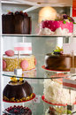 Confectionery store detail on the caked display with different cakes and pastries shelves behind a glass counter Stock Images