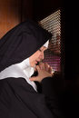 Confessing sins nun kneeling in a confession booth with a priest on the other side Royalty Free Stock Photo