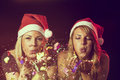 Confetti two young girls wearing santa s hats blowing away colorful at new year a eve party Royalty Free Stock Image