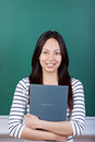 Confident asian woman holding application folder with and blackboard in background Royalty Free Stock Image
