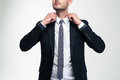 Confident attractive young businessman adjusting his collar over white background Royalty Free Stock Image