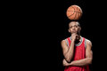 Confident basketball player posing with ball on head on black Royalty Free Stock Photo