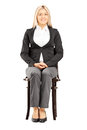 Confident blond businesswoman in suit sitting on a chair wooden isolated white background Royalty Free Stock Image
