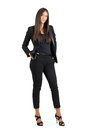 Confident bossy business woman in black suit with hands in pockets looking at camera full body length portrait isolated over white Stock Images