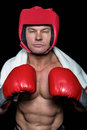 Confident boxer against black background with gloves and headgear Stock Photos