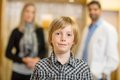 Confident boy with optometrist and mother at store portrait of in background Stock Image