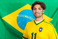 Confident brazilian supporter standing in front of brazilian fla portrait young sports fan against flag Stock Photo