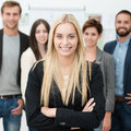 Confident business team with a successful young businesswoman in the foreground smiling at the camera with folded arms Royalty Free Stock Photos