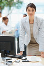 Confident  business woman at desk with colleagues Royalty Free Stock Photography