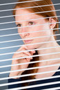 Confident business woman in thought a young businesswoman while looking through open window blinds at an office Stock Photography