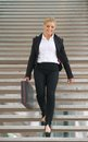 Confident business woman walking downstairs with briefcase portrait of a Stock Photos