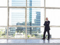 Confident businessman with arms crossed standing by window full length portrait of middle age in office Royalty Free Stock Photo