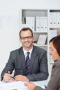 Confident businessman in his office seated at desk working with a female colleague looking to to smile at the camera Royalty Free Stock Images