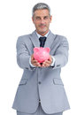 Confident businessman holding piggy bank in both hands on white background Stock Photo