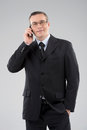 Confident businessman middle age man in formalwear talking on the mobile phone isolated on grey Royalty Free Stock Photo
