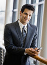 Confident businessman text messaging on cell phone Stock Photos