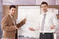 Confident businessmen presenting together smiling two over whiteboard Stock Photos