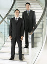 Confident businessmen standing on stairs full length portrait of two Stock Photos