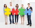Confident businesspeople joining puzzle pieces Royalty Free Stock Photo