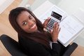Confident businesswoman calculating tax at desk Royalty Free Stock Photo