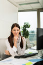 Confident businesswoman in office young sitting at desk Stock Images