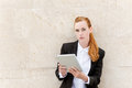 Confident businesswoman reading tablet pc young redhead against the wall Royalty Free Stock Photos