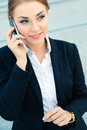 Confident businesswoman talking on business phone handsome and or female manager cell walking in front of modern architecture Royalty Free Stock Image