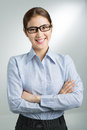 Confident businesswoman vertical portrait of a smiling business lady posing at camera on grey Royalty Free Stock Photo