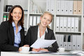 Confident businesswomen sitting at office desk portrait of Royalty Free Stock Image