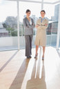 Confident businesswomen standing in bright office with arms crossed Royalty Free Stock Images