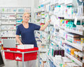 Confident chemist arranging medicines in shelves portrait of mature female at pharmacy Royalty Free Stock Image